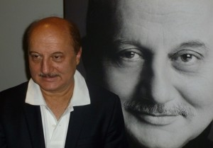Anupam Kher in front of a large poster of his book