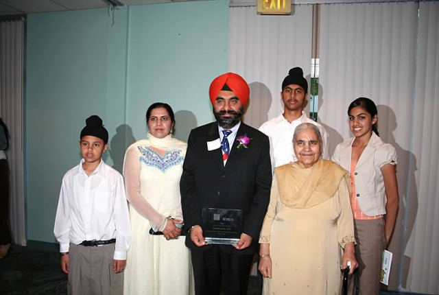 Dr Kang posing with his family after winning the Unsung Hero Award for community service.