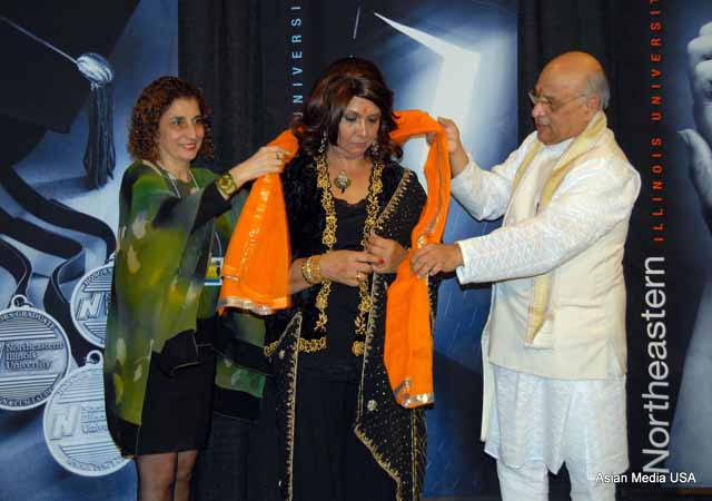 Director of NEIU Asian and Global Resource Center at the Angelina Pedroso Center for Diversity and Intercultural Affairs, Yasmin A. Ranney (C) receives an orange sash from Saba Ayman-Nolley (L) and Rohit Joshi (R) for her services and for emceeing the gala.