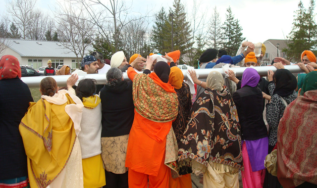 Devotees cleaning the pole before hoisting the Sikh flag of Nishan Sahib.