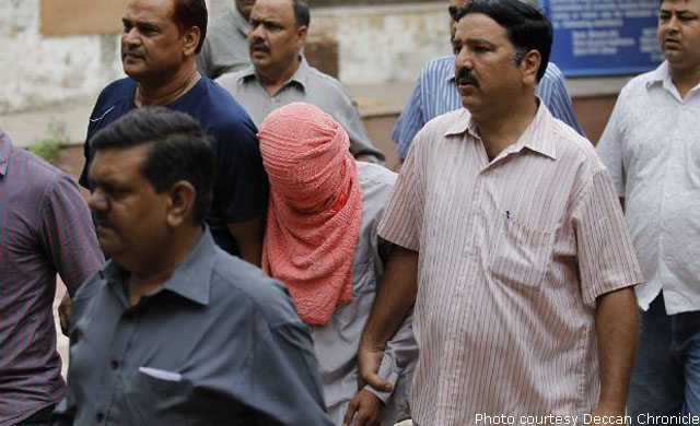 With his face covered, the juvenile rapist in Delhi gangrape case is being led away by cops in plainclothes