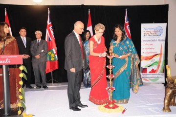 Ontario Premier Kathleen Wynne lights Diwali lamp. Indian consul general Dinesh Bhatia is to her right and Panorama India chairperson Anu Srivastava to her left.