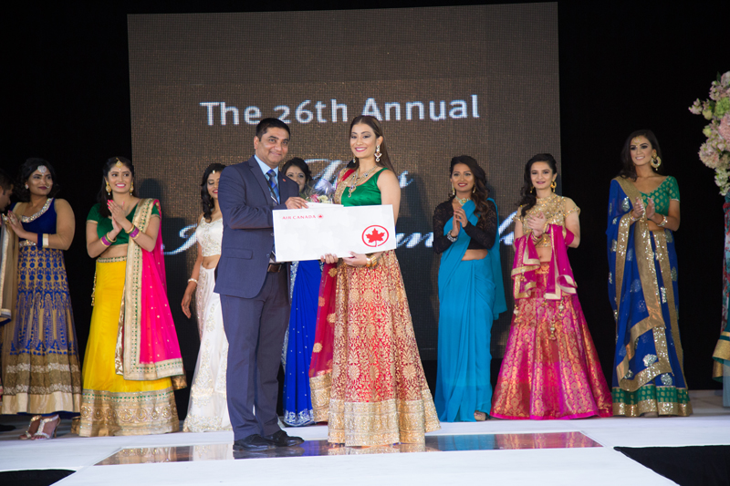 Ria Tharakan of Mississauga receiving the Air Canada People's Choice Award from Girish Kadam, Manager (Speciality Sales), Air Canada Leisure Group.