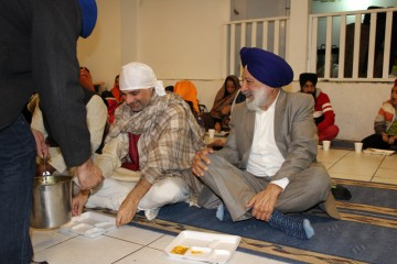 Indian consul general Dinesh Bhatia sitting for the langar.