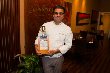 Chef Sid poses with his award inside his trendy restaurant on Commercial Drive in Vancouver.