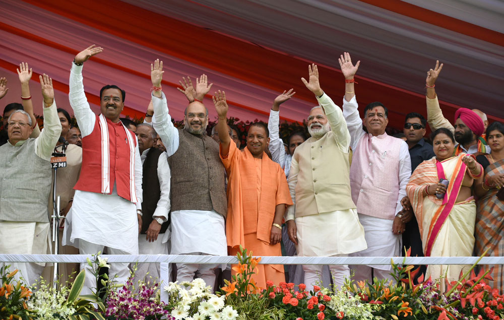 Prime Minister Narendra Modi at the swearing-in ceremony of Yogi Adityanath (yellow robes) in Lucknow on March 19.